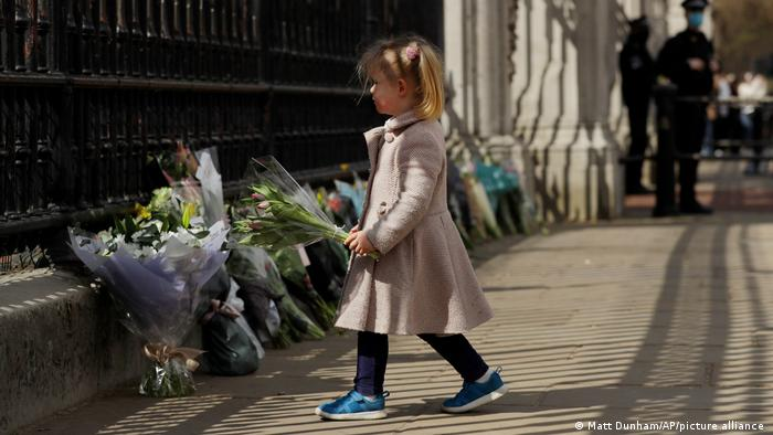 A young girl lays flowers at Buckingham Palace