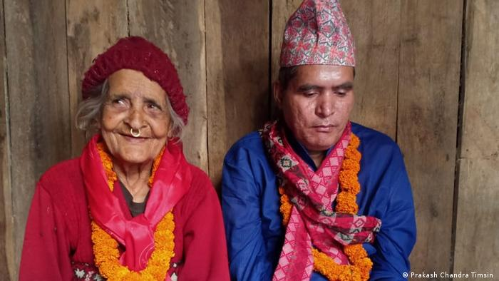 Durga Prasad Timsina sits with his mother