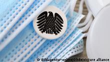 Schutzmasken, Desinfektionsmittel und deutscher Bundesadler, Symbolfoto Nationale Gesundheitsreserve