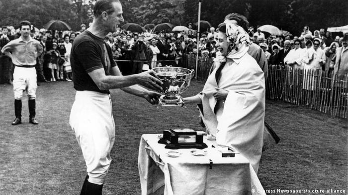 La reina Isabel II le entrega un trofeo a su esposo, el príncipe Felipe.