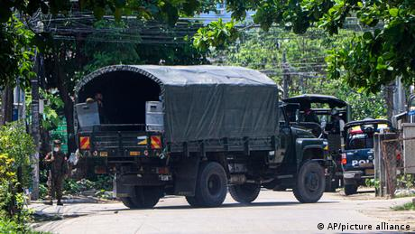 A police vehicle is parked at a road to block anti-coup protesters' gathering in Yangon, Myanmar