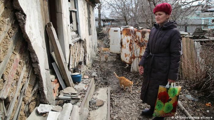 A woman visits her home in the separatist-controlled territory to collect her belongings after a recent shelling near a frontline outside Donetsk, eastern Ukraine,