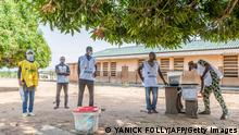 Electoral commission officials set up a ballot boxes at a polling station at the Dakpa primary school in Save, Benin, on April 11, 2021, while waiting for voters. - On April 8, 2021, in the central city of Save, two people died and five others suffered gunshot wounds after troops fired tear gas and live rounds in the air to break up a demonstration. The streets of Save were empty on April 11, 2021, with all businesses closed. Soldiers were patrolling in the city. (Photo by Yanick Folly / AFP) (Photo by YANICK FOLLY/AFP via Getty Images)