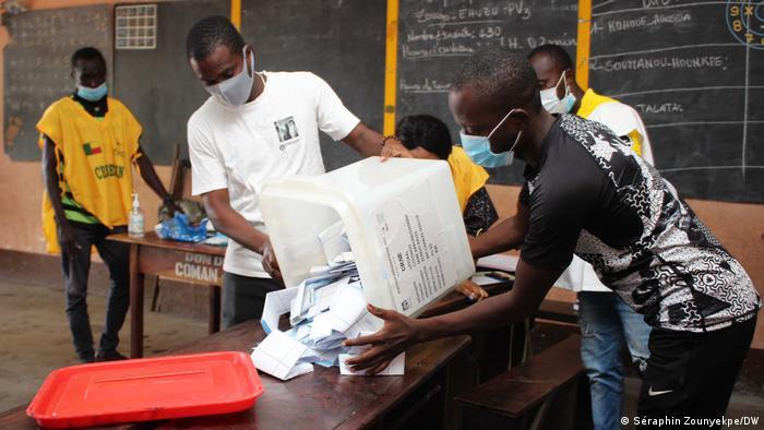 Foto de dos personas que abren una urna de votos en Benin.