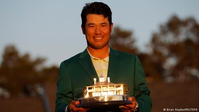 Hideki Matsuyama holds a golfing trophy while wearing a green jacket