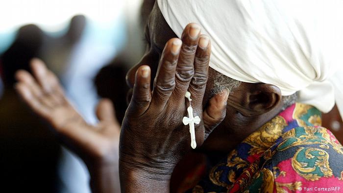 Foto simbólica de una mujer haitiana con un rosario en la mano.