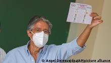 Guillermo Lasso, Präsidentschaftskandidat der Partei «Chancen schaffen» (CREO), trägt einen Mund-Nasen-Schutz und hält seinen Stimmzettel in einem Wahllokal hoch. In der Stichwahl treten der konservative Banker Lasso und der Linkskandidat Arauz gegeneinander an. Im Mittelpunkt des Wahlkampfes stand die angespannte wirtschaftliche Lage in dem südamerikanischen Land. +++ dpa-Bildfunk +++