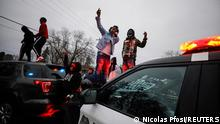 Demonstrators stand on a police vehicle during a protest after police allegedly shot and killed a man, who local media report is identified by the victim's mother as Daunte Wright, in Brooklyn Center, Minnesota, U.S., April 11, 2021. REUTERS/Nick Pfosi