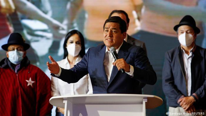 Ecuador Präsidentschaftswahlen - Andres Arauz mit Mikrofon in in der Hand am Rednerpult. Hinter ihm vier Menschen mit Mundschutz.