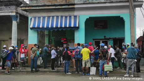 People wearing face masks line up to buy food in Havana