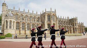 Four Royal Hussars soldiers march past St. George's Chapel