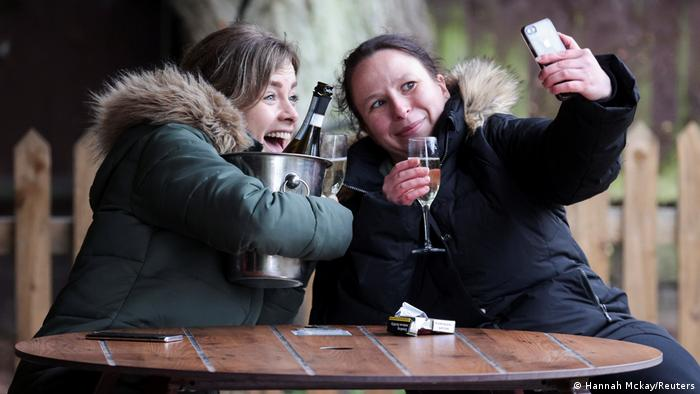 Women take a selfie over drinks in London after the UK reopens pubs