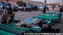 Mulher sentada, homem deitado na rua entre bujões de oxigênio num subúrbio de Lima, Peru