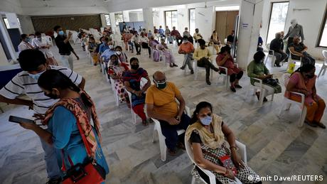 People sit in a waiting area to receive a dose of COVISHIELD