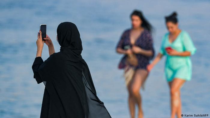 امرأتان تمشيان على الشاطئ في دبي وآخرى محجبة تصور