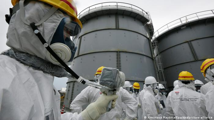 People in suits measure radiation levels at the Fukushima Daiichi nuclear power plant