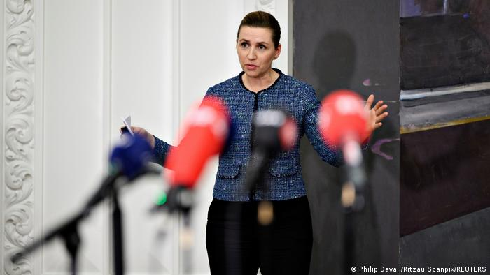Prime Minister Mette Frederiksen gestures in front of microphones