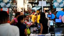 Customers stand in lines at the cashiers of a store that accepts the Venezuelan cryptocurrency Petro