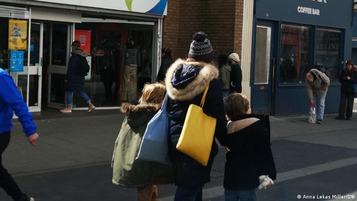 Mulher carregada de compras e duas crianças em rua de pedestres