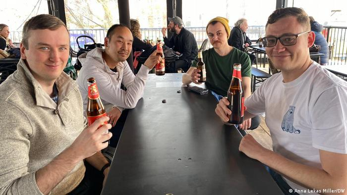 Four friends in London enjoy a beer together on the first day that the UK lifts lockdown restrictions