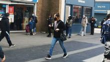 A woman walks on Walthamstow's High Street, the first day that the UK lifts lockdown restrictions