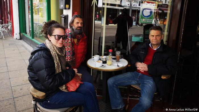 Three Londoners sit at a table and drink coffee on Walthamstow's High Street