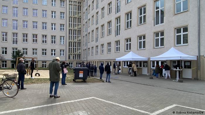 Auf einem Platz vor einem großen grauen Gebäude mit vielen Fenstern, das über Eck mehr als die Hälfte des Bildes füllt, stehen etliche Menschen in Warteposition vor zwei überdachten Schaltern