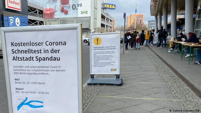 Einlasskontrolle vor dem Ikea-Möbelhaus in Berlin-Spandau: am rechten Bildrand sitzen mehrere Personen an Tischen. Auf dem Bürgersteig in der Bildmitte stehen hinten mehrere Personen in einer Warteschlange, links vorne informieren aufgestellt Tafeln üb er den Ort für kostenlose Corona-Schnelltests in Spandau und die Testpflicht