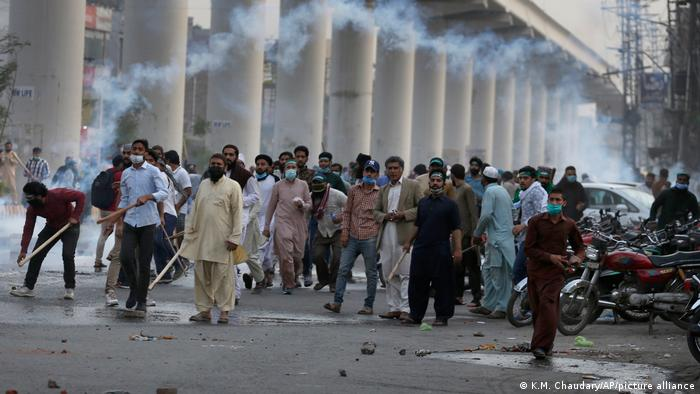 Supporerts of the TLP throw stones towards police firing tear gas to disperse them