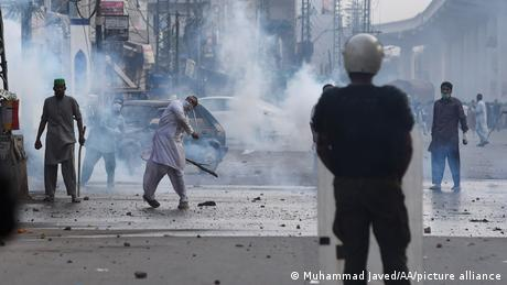 Pakistani Islamists of Tehreek-e-Labbaik Pakistan (TLP) throw stones against police who use teargas against anti-France Islamist protesters during a protest in Lahore, on April 12, 2021