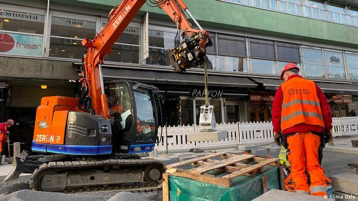 Una excavadora eléctrica naranja en una obra en Oslo. Un hombre con chaleco naranja y casco se encuentra en primer plano.