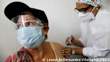 An elderly woman receives a dose of Russia's Sputnik V coronavirus disease (COVID-19) vaccine in Caracas