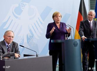 Merkel and Issing (r) with German Finance Minister Wolfgang Schaeuble (seated)