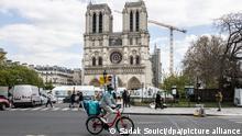 Ein Fahrradfahrer fährt an der Kathedrale Notre-Dame vorbei