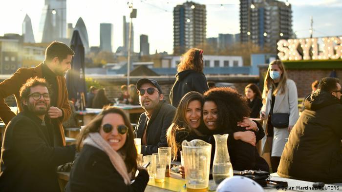 Eine Gruppe von Freunden trinkt auf einem Dachrestaurant in London