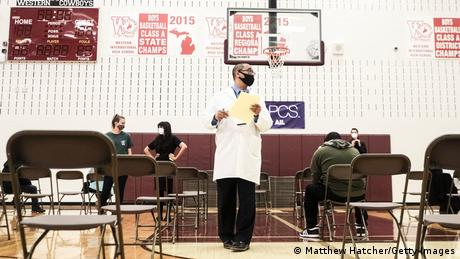 Medical staff in a high school in Detroit watch vaccination patients