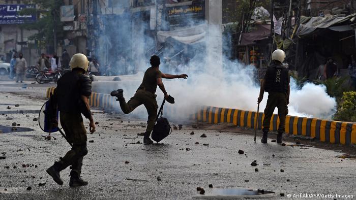 A policeman throws a stone towards supporters of Tehreek-e-Labbaik Pakistan