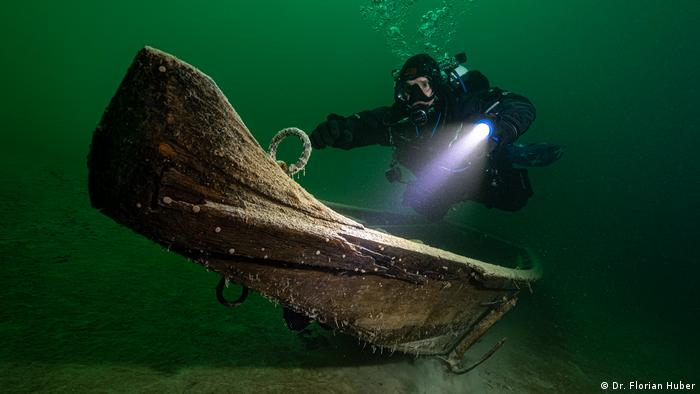 A diver uses a flashlight to illuminate an ancient wooden boat.