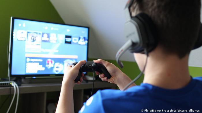Jovem com fone de ouvido joga videogame