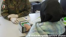 11.11.2015 A German defense soldier takes the fingerprints of an asylum seeker from Syria in the 'waiting centre' set-up for refugees in Erding, Germany, 11 Novmeber 2015. The soldiers are there provide registration assistance for the Federal Office for Migration and Refugees (BAMF). In the short-term accomodation is on the site of an air base of the German army and is housing up to 5000 migrants in tents and aircraft shelters. Photo: ARMIN WEIGEL/dpa
