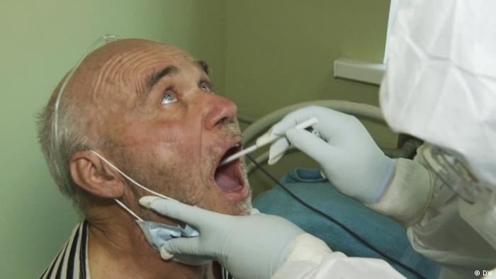 у пожилого мужчины врач берет мазок для теста на ковид
