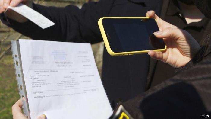 Поліцейська фотографує фальшиву довідку про результат тесту на коронавірус