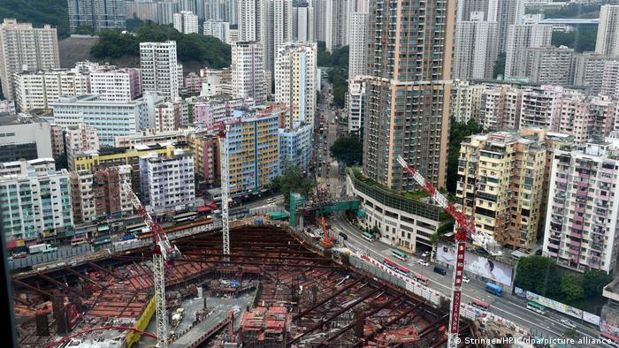 Grúas y obras de construcción frente a edificios de gran altura en Hong Kong.