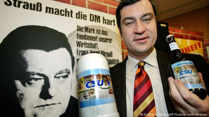 Söder posing with beer mug in front of Strauss campaign ad