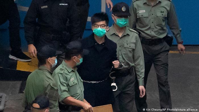 Der Hongkonger Demokratie-Aktivist Joshua Wong wird gefesselt mit Handschellen von Polizisten abgeführt