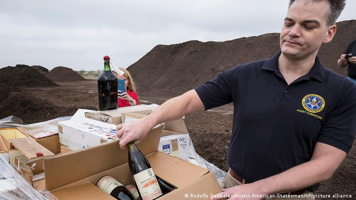 Jason Martinez, U.S. Marshals, assistant program manager, with the Asset Forfeiture Division, shows one of the 500 plus bottles of counterfeit and unsellable wine being prepped for destruction at the Texas Disposal Systems recycling and compost facility in Austin, Texas.