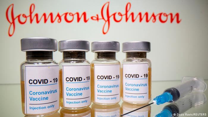 Vials with a sticker reading, COVID-19 / Coronavirus vaccine / Injection only and a medical syringe are seen in front of a displayed Johnson & Johnson logo