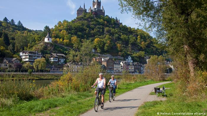 A couple of cyclists riding along a riverside bicycle path with the village of Cochem on the far banks, Germany
