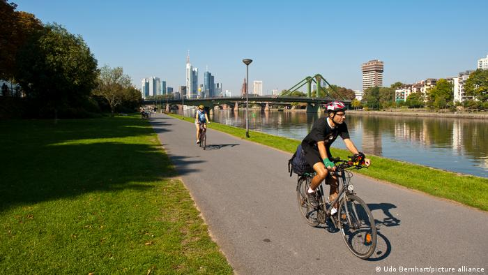 Two mountain bikers on a riverside cycle path passing the city of Frankfurt am Main, Germany
