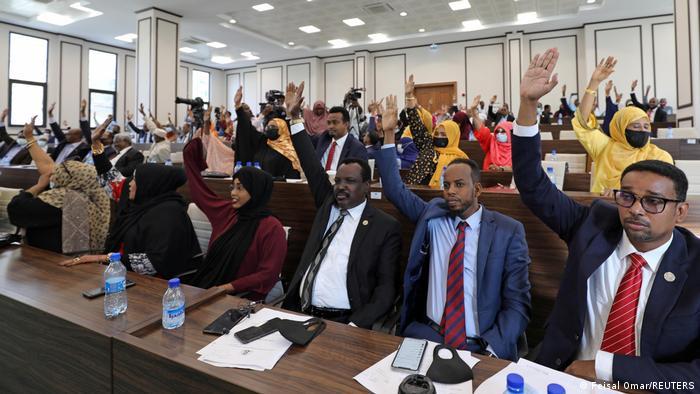 Abgeordnete des somalischen Parlaments sitzen in Bankreihen und heben zur Abstimmung die Hand